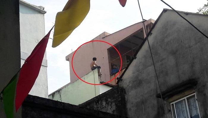 Thanh niên ngáo đá cầm dao ngồi vắt vẻo trên nóc nhà 3 tầng