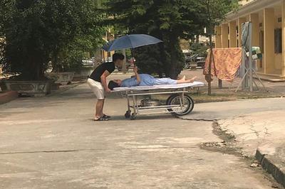 Vợ bụng bầu che ô cho chồng loay hoay đẩy xe vào phòng sinh