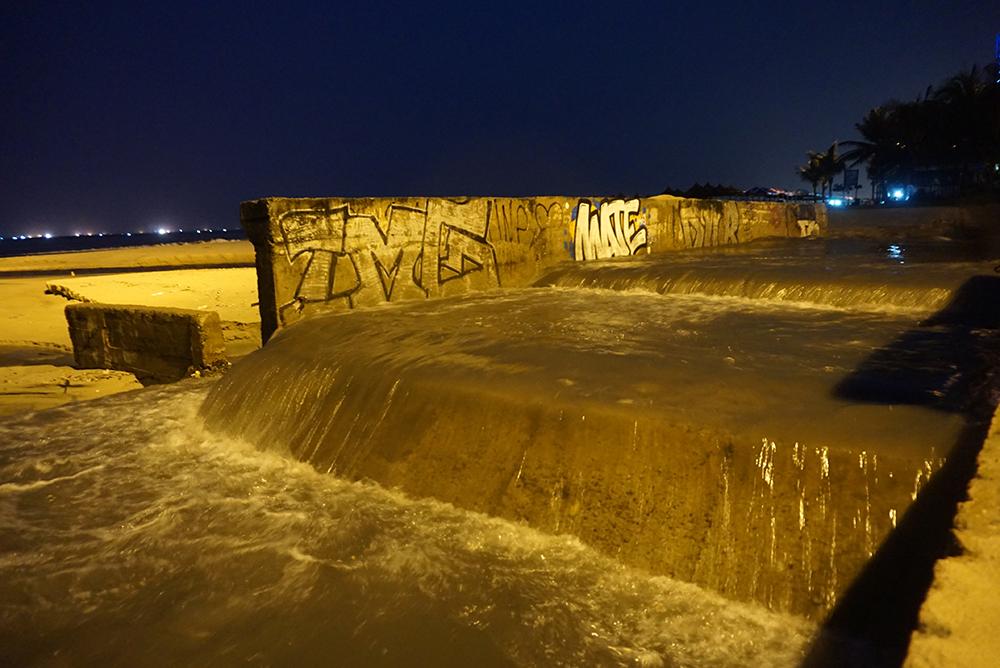 Sau mưa lớn, nước đen ngòm hôi thối cuồn cuộn đổ xuống biển Đà Nẵng