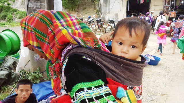 Children carried by mothers at Bac Ha Market