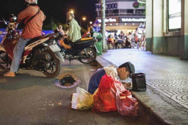 Hình ảnh mẹ cầm tay con dạy từng nét chữ bên lề đường gây xúc động mạnh