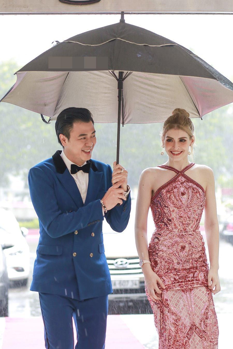 Tuấn Tú che ô cho An Tây vượt mưa bão dự sự kiện