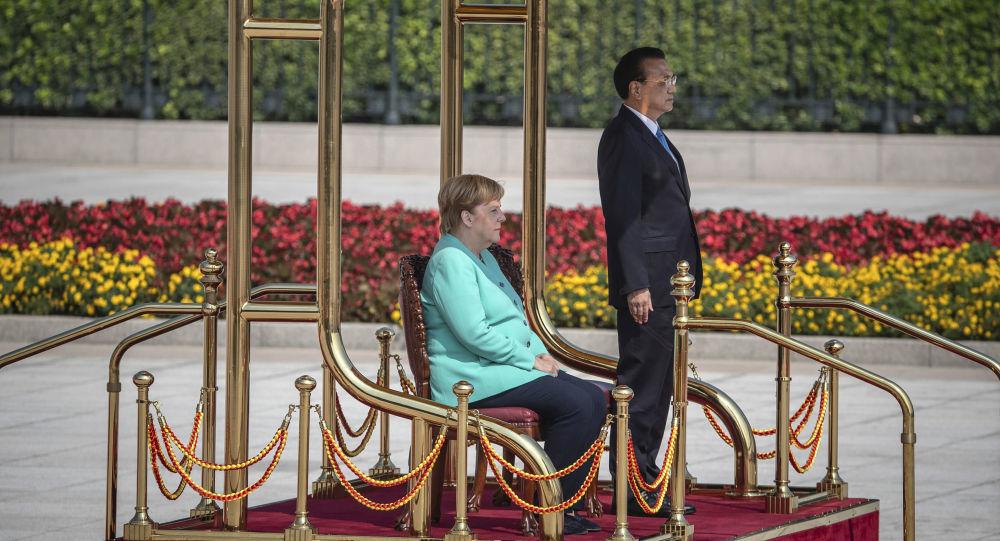 Thủ tướng Đức Merkel ngồi trong lễ chào cờ khi thăm Trung Quốc