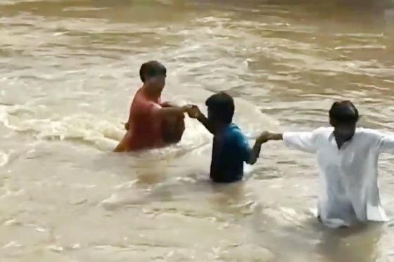 Xem dân làng tạo 'dây chuyền người' giải cứu bé gái giữa nước lũ cuồn cuộn