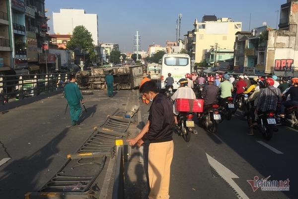 Xe tải lật trúng 2 xe máy, ép cô gái kẹt cứng vào thành cầu ở Sài Gòn
