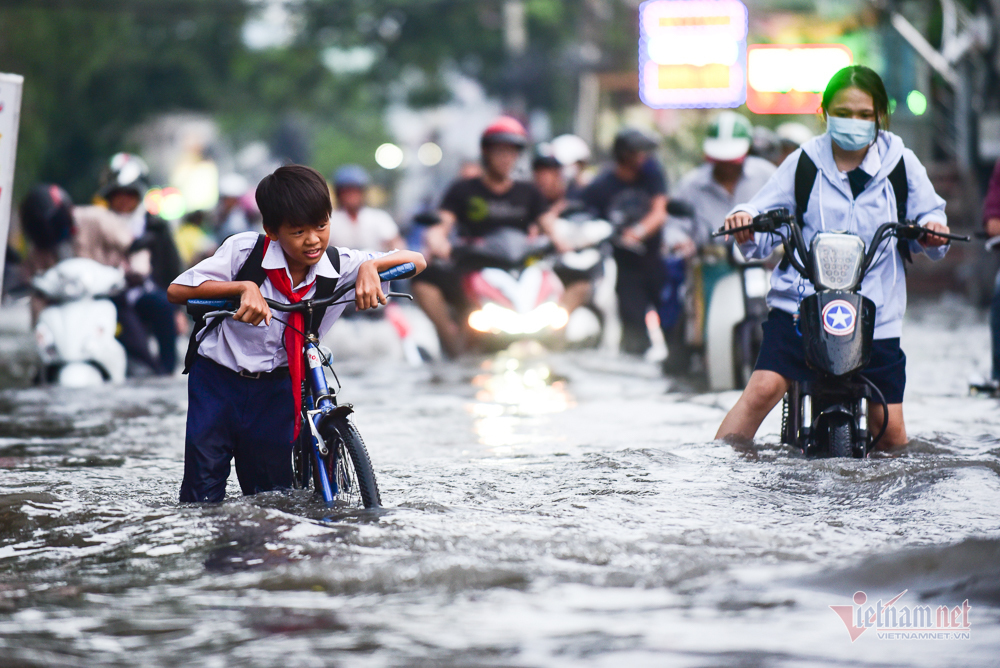 Mẹ bồng con mò mẫm lội đường Sài Gòn ngày triều cường kỷ lục