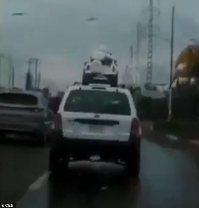 Giật mình cảnh 2 trẻ nhỏ ngồi trên nóc ô tô giữa trời mưa