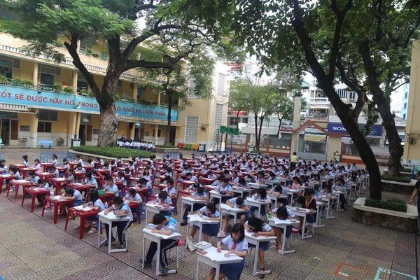 Học sinh tiểu học ngồi thẳng tắp thi vẽ giữa sân trường