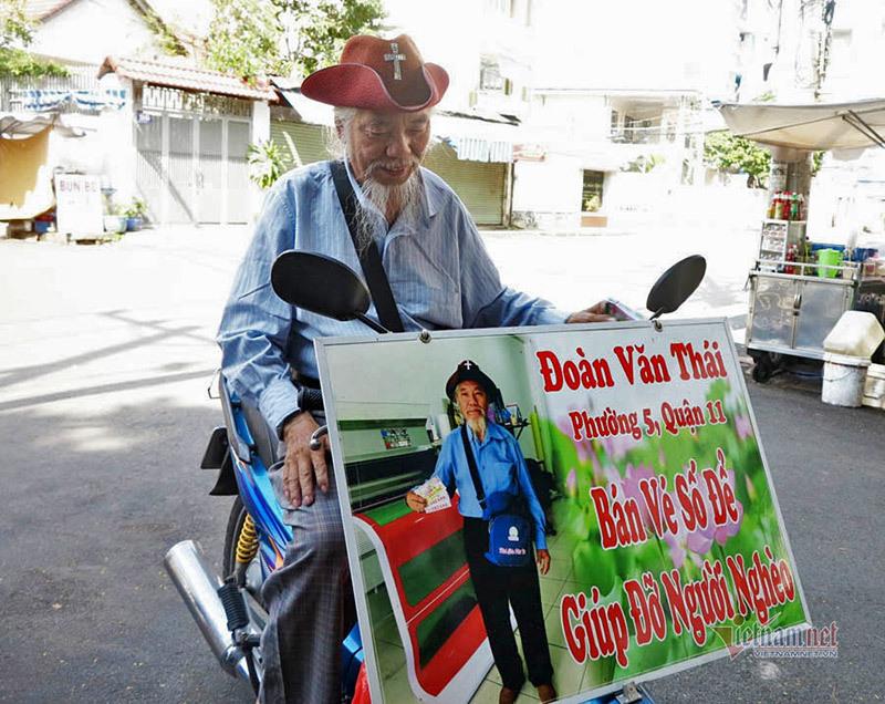 Chiếc biển ghi: Đoàn Văn Thái, Phường 5, Quận 11 bán vé số giúp đỡ người nghèo' được ông gắn cố định trước xe.