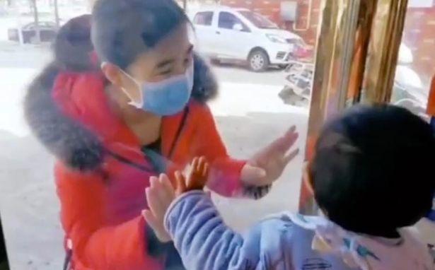 Nữ y tá TQ hôn con qua lớp kính sau gần 1 tháng xa cách chống Covid-19
