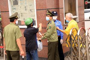Bị từ chối tiếp tế, cố đưa đồ qua khe cổng bệnh viện Bạch Mai