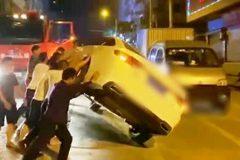 Người dân hợp lực lật chiếc ô tô để thông đường cho xe chữa cháy