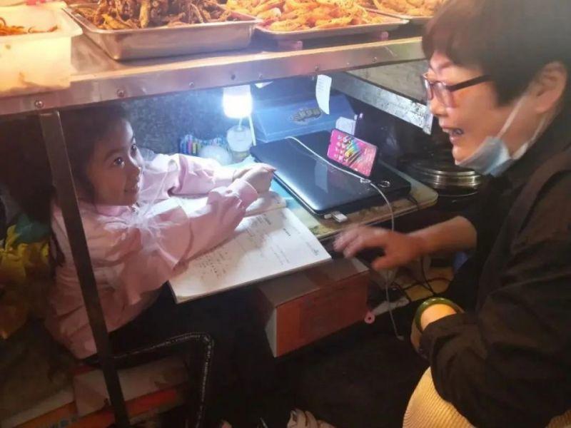 Cô bé 7 tuổi học bài dưới gầm sạp hàng của mẹ