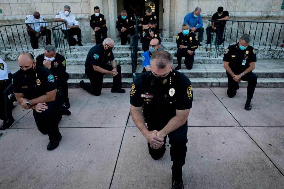 Cảnh sát Mỹ quỳ gối, ôm người biểu tình thể hiện tình đoàn kết