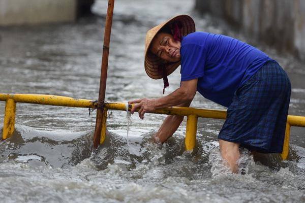 Mưa tối trời 30 phút, dân Sài Gòn móc cống dọn rác, dìu nhau qua đường ngập