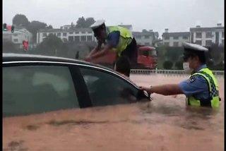 Cảnh sát TQ đập kính chắn gió ôtô cứu người mắc kẹt trong lũ