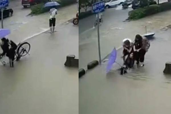 Cô gái đạp xe rơi vào hố lụt giữa phố Trung Quốc