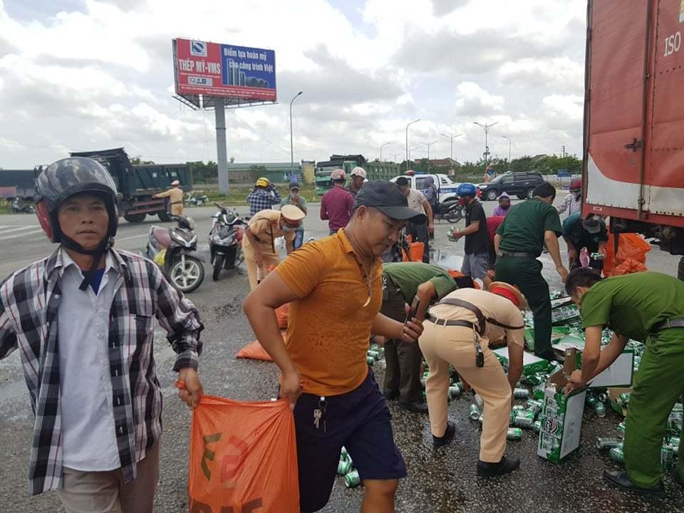 Xe tải chở bia đổ ra đường, công an cặm cụi gom giúp tài xế
