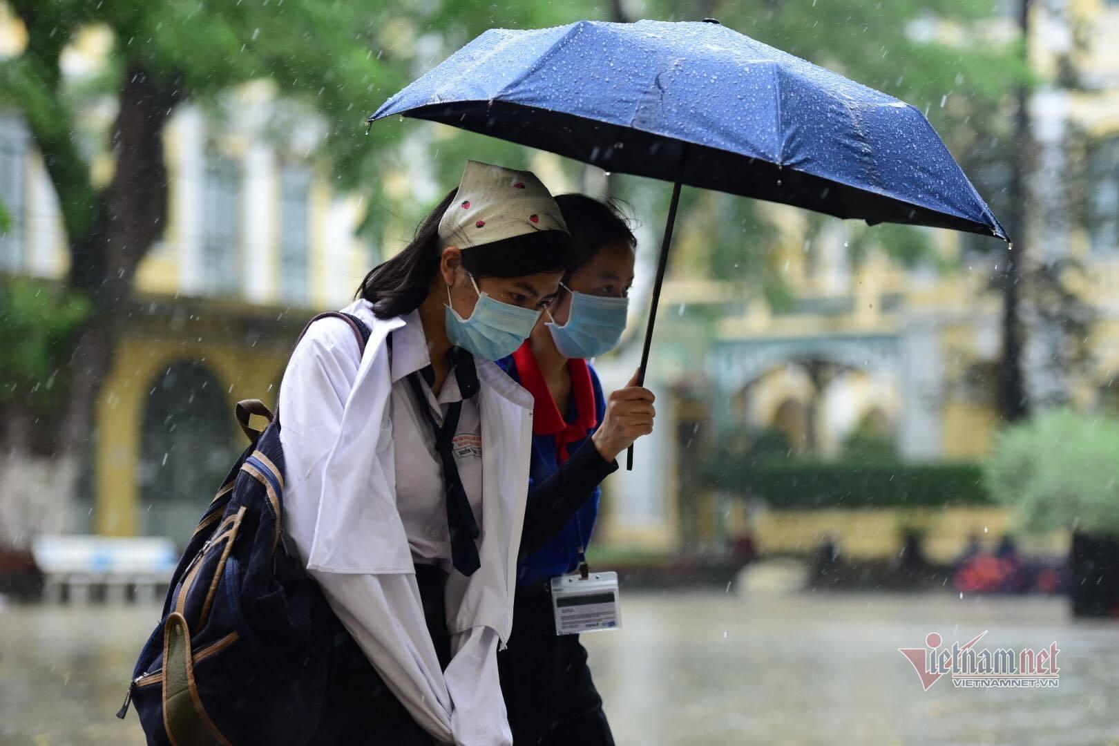 Thí sinh đến trường thi môn Toán trong cơn mưa