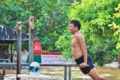 Người dân Hà Nội bì bõm tập thể dục, tắm giữa nước lũ sông Hồng