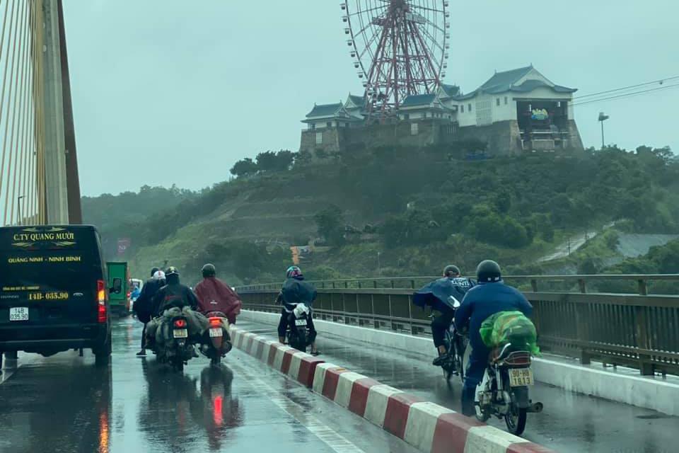 Ô tô đi chậm 'dìu' xe máy qua cầu Bãi Cháy trong gió bão