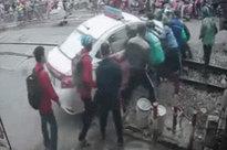 Clip: Cố lao qua rào chắn, taxi bị mắc kẹt trên đường ray, người dân tá hoá giải cứu - 2 phút căng thẳng cao độ