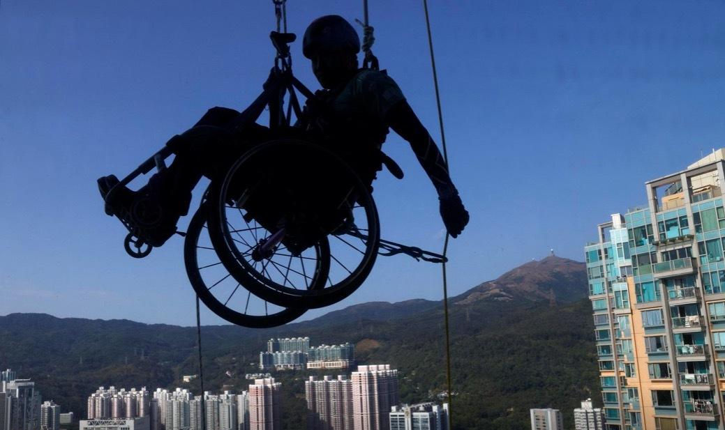 Người đàn ông ngồi xe lăn leo cao ốc chọc trời