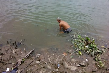 74-year-old man helps Saigonese cope with floods by clearing canals
