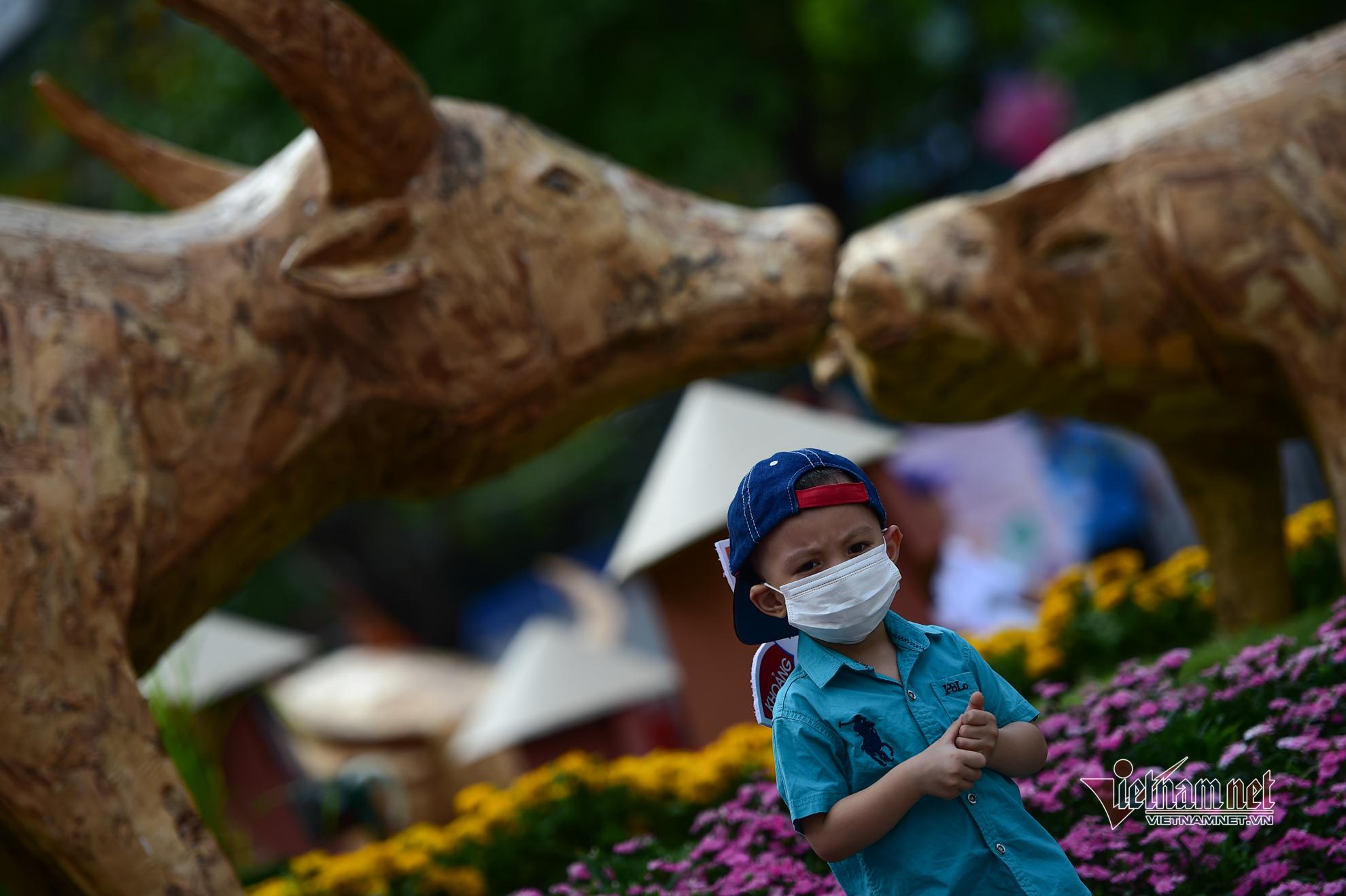 Người Sài Gòn đeo khẩu trang du xuân, tạo dáng bên đường hoa Nguyễn Huệ