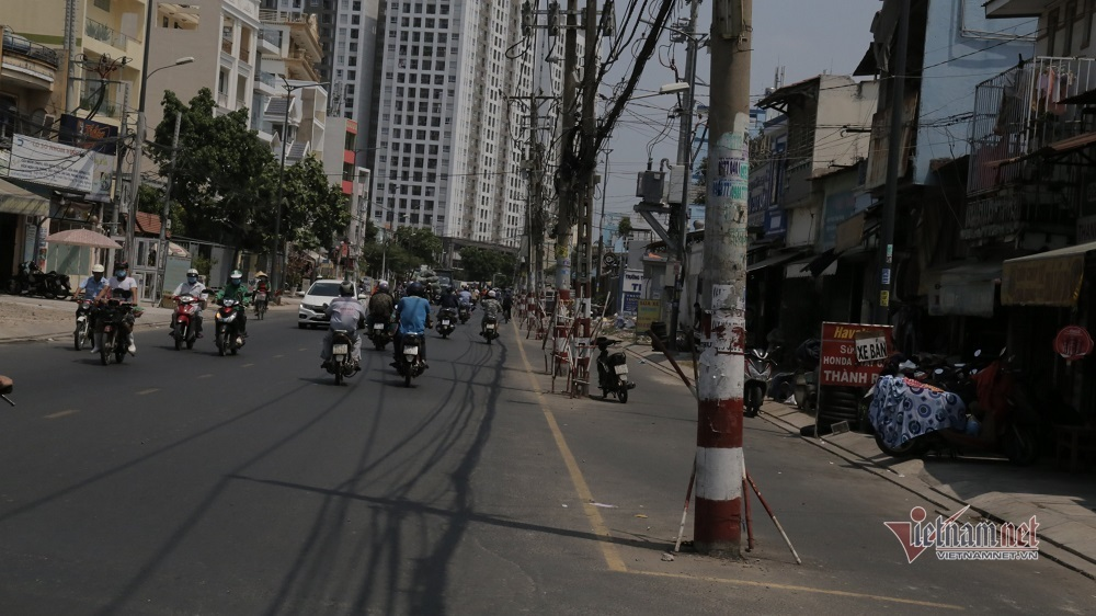 Trăm cột điện ngả nghiêng giữa đường Sài Gòn, dân luồn lách đi như 'diễn xiếc'