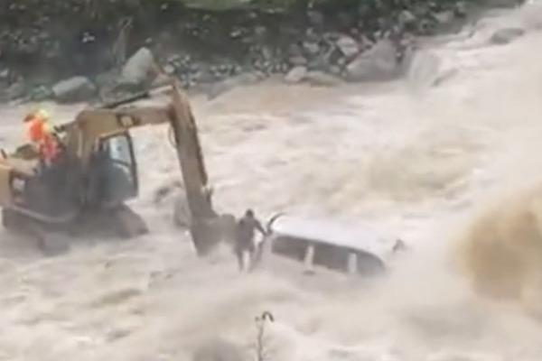 Máy xúc giải cứu tài xế ô tô dưới sông lũ cuồn cuộn