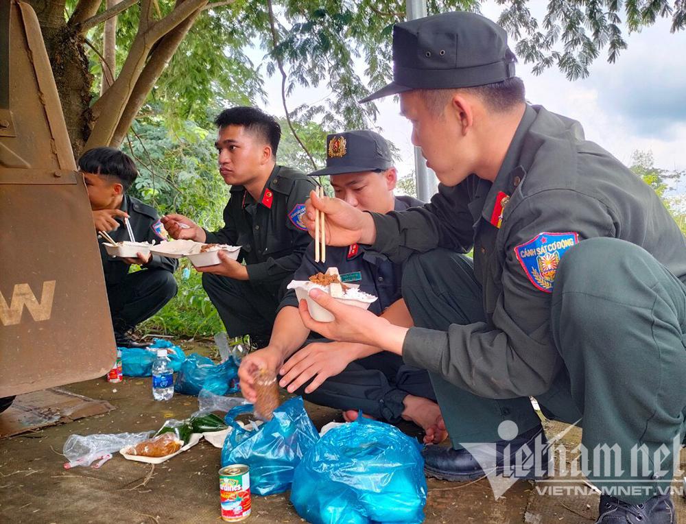 Cảnh sát cơ động ăn cơm hộp trên đường hành quân thần tốc đi chống dịch