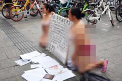 Hai người phụ nữ mặc nội y quỳ gối trên đường gây tranh cãi