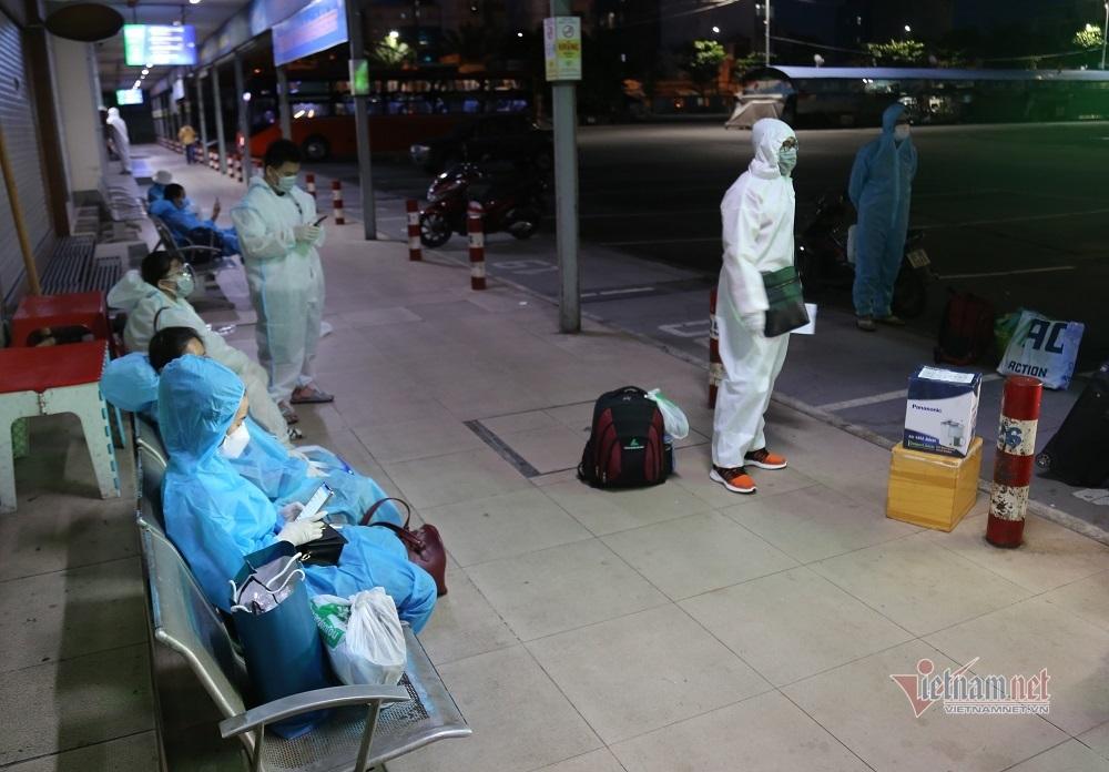 Người dân mặc đồ bảo hộ kín mít đến bến xe Miền Đông về quê giữa đêm