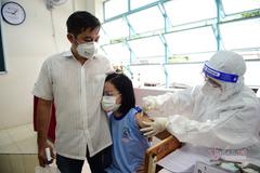 Cảnh phụ huynh theo con đi tiêm vắc xin Covid-19 ở TP.HCM
